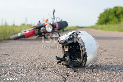 istock Photo of helmet and motorcycle on the road, the concept of road accidents 1016769248