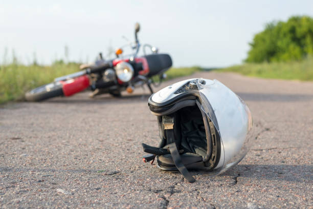 photo of helmet and motorcycle on the road, the concept of road accidents - motorcycle stock photos and pictures