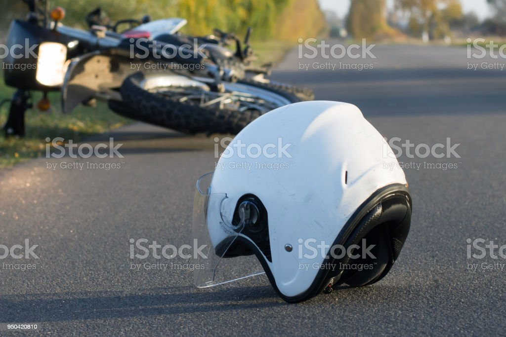 Photo of helmet and motorcycle on the road, the concept of road accidents – zdjęcie
