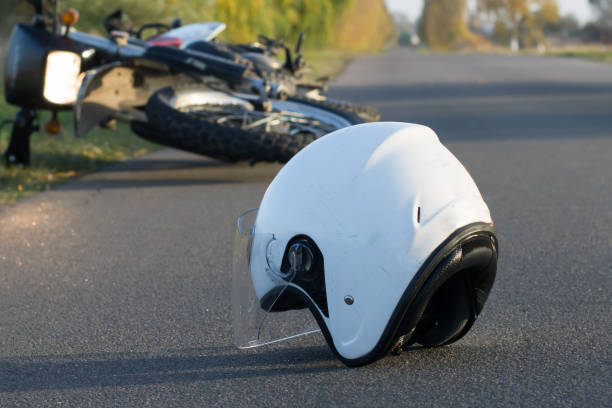 Photo of helmet and motorcycle on the road, the concept of road accidents Photo of helmet and motorcycle on road, the concept of road accidents misfortune stock pictures, royalty-free photos & images