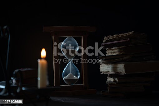 Photo of hourglass and hardcover antique books under candlelight in dark. No people are seen in frame. Shot with a full frame mirrorless camera.