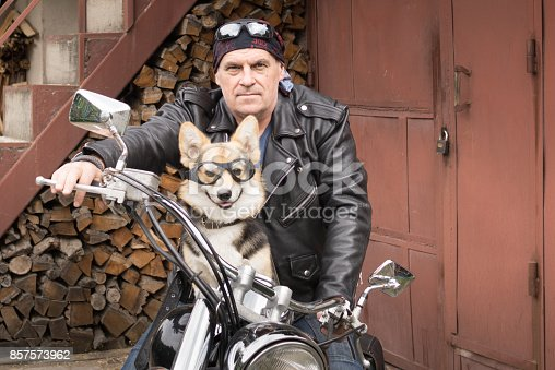 istock Photo of humor. The biker and his dog are sitting on a motorcycle. 857573962