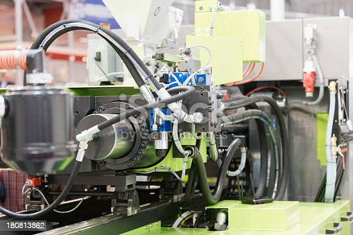 A industrial plastic injection molding machine.  The machine features gray tubes, clear plastic joiners, red wires and various other parts.  The close-up view of this industrial machine creates an abstract effect with a mixture of gray, green, red, blue and yellow colors.
