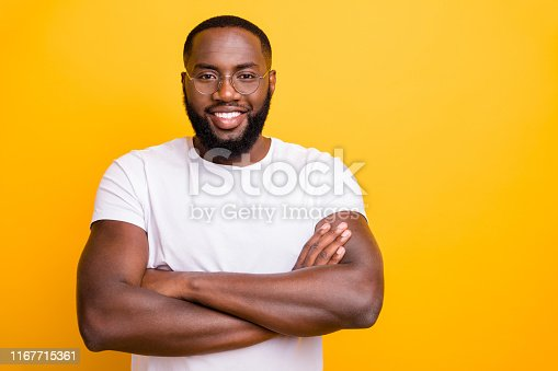 1163696387 istock photo Photo of intelligent clever american guy standing with his hands crossed while isolated with yellow background 1167715361