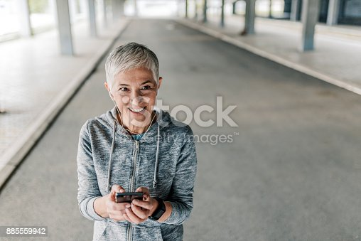 istock Photo of jogging woman setting music and running route on smart phone 885559942