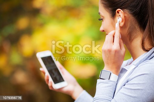 Photo of joyful fitness woman 20s in sportswear touching bluetooth earpod and holding mobile phone, while resting in green park.