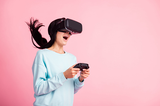 Photo of lady using vr 3d spectacles amazing reality effect play games joystick wear pullover isolated pink color background
