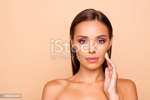 Photo of lady with shoulders she isolated on pastel beige background with copy space for text she look at camera touch her cheek by hand