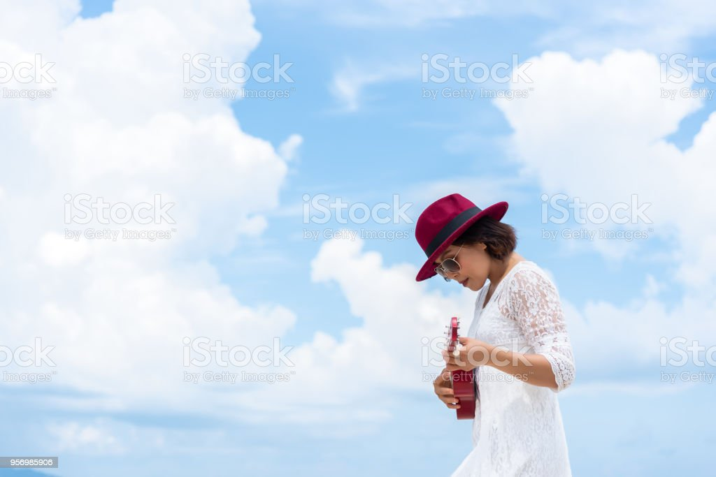 Photo of left side women wearing white dress, red hat playing ukulele outdoor with blue sky and white clouds background. Travel and summer concept. stock photo