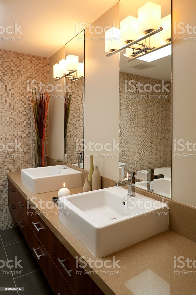Photo of lit bathroom with modern his and hers sinks royalty-free stock photo