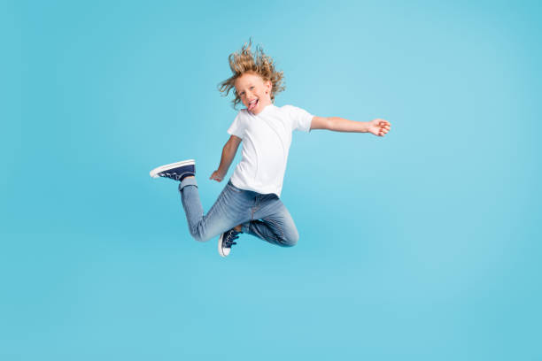 Photo of little child jump raise legs stick-out tongue wear white shirt jeans sneakers isolated blue color background stock photo