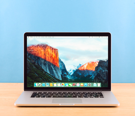 Moscow, Russia - February 19, 2016:  Photo shoot of Macbook Pro on blue background.  MacBook is a brand of notebook computers manufactured by Apple Inc.