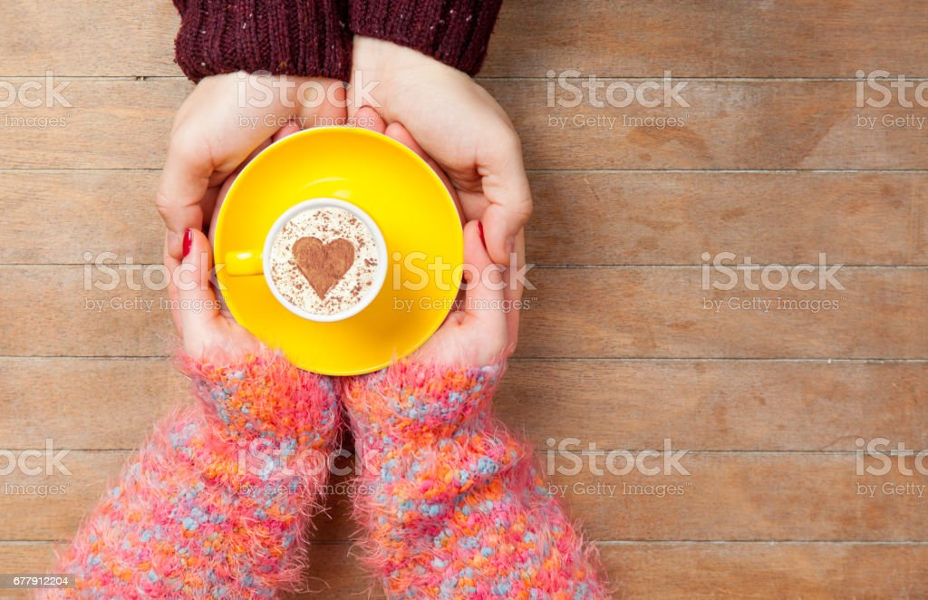 photo of male and female hands holding cup of coffee on the wonderful brown wooden background royalty-free stock photo