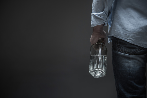 istock Photo of male back holding bottle in hand 665992172