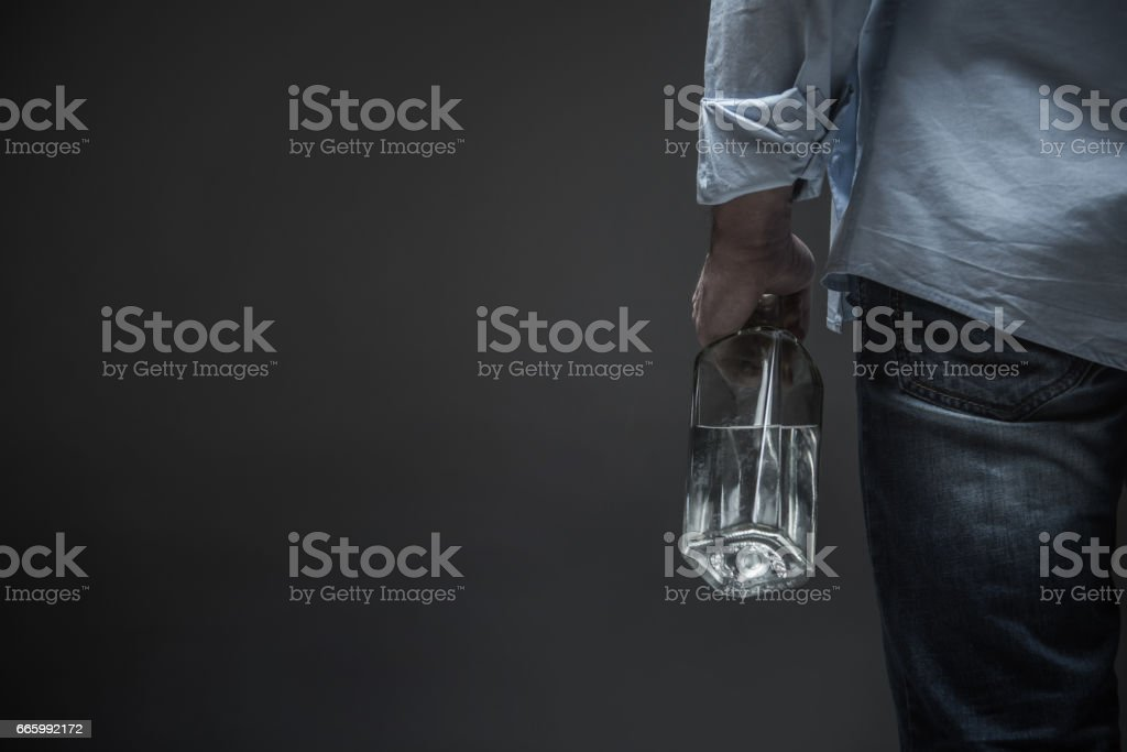 Photo of male back holding bottle in hand stock photo