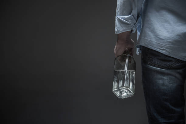 photo of male back holding bottle in hand - dipsomania stock pictures, royalty-free photos & images