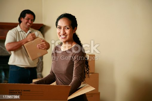 istock Photo of man and woman unpacking brown boxes on moving day 172957394