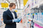 istock Photo of man dressed in formal suit, covers mouth with medical mask, wears rubber gloves to prevent virus spreading, poses in supermarket in washing agent department, holds household detergent 1219973923