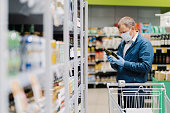 istock Photo of man in protective medical mask and rubber gloves to prevent coronavirus, poses in supermarket, holds glass bottle of alcoholic drink, reads label, makes shopping during quarantine time 1219973960