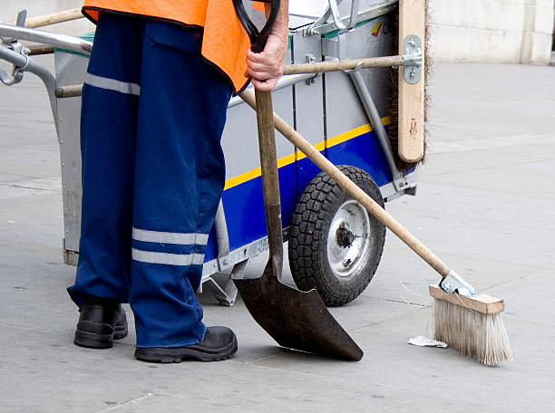 Photo of man in uniform cleaning street