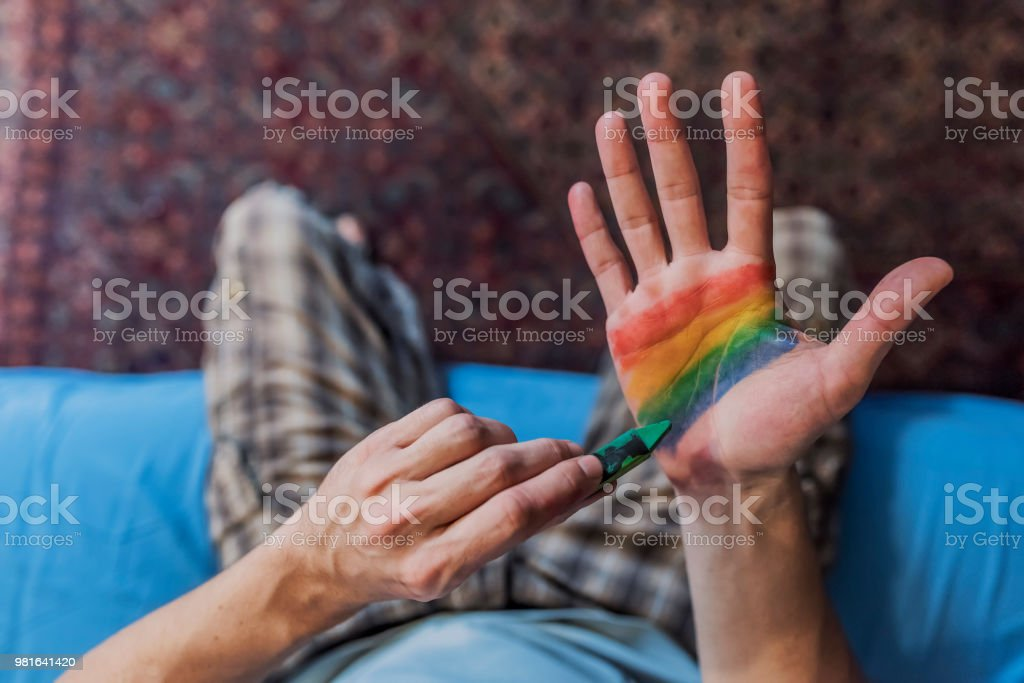 Photo of Man painting colored flag on hand stock photo