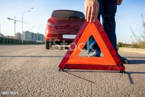 istock photo of man putting triangle warning sign on road 500178701