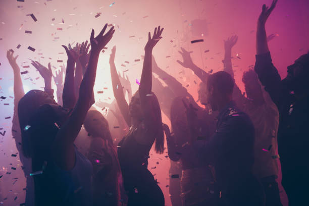 Photo of many birthday event people dancing colorful lights confetti flying enjoy nightclub hands raised up wear shiny clothes Photo of many birthday event people dancing colorful lights confetti, flying enjoy nightclub hands raised up wear shiny clothes prom night stock pictures, royalty-free photos & images