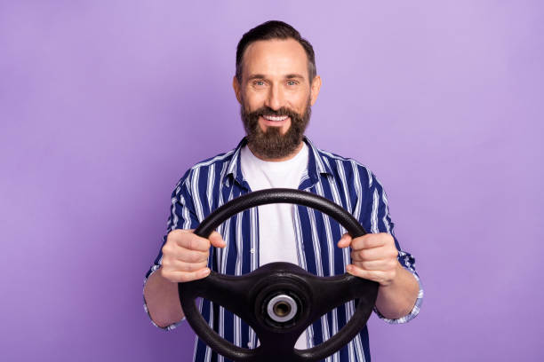 Photo of mature man driver hold steering wheel isolated over purple color background stock photo