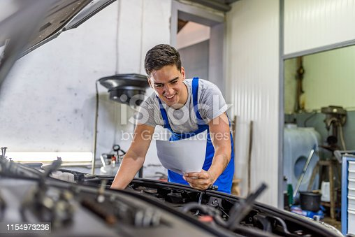 istock Photo of Mechanic working on car in his shop 1154973236