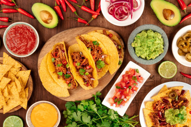 A photo of Mexican food, including tacos, guacamole, pico de gallo, nachos and others, shot from the top with ingredients on a dark rustic wooden background stock photo