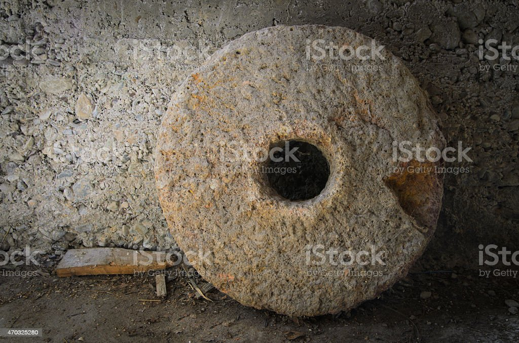 Photo of millstone leaning against wall stock photo