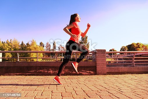 istock Photo of modern young woman in sports clothing jumping while exercising outdoors. 1170148754