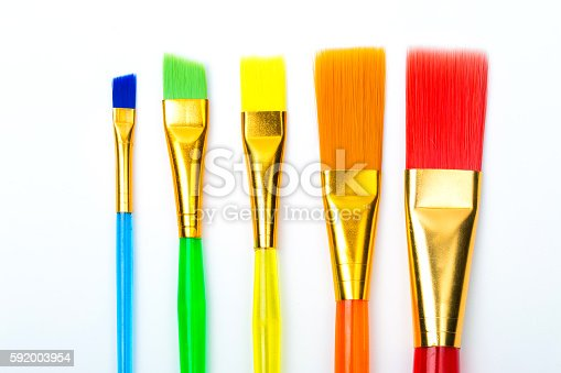 istock Photo of multicolor paint brushes isolated on white background. 592003954