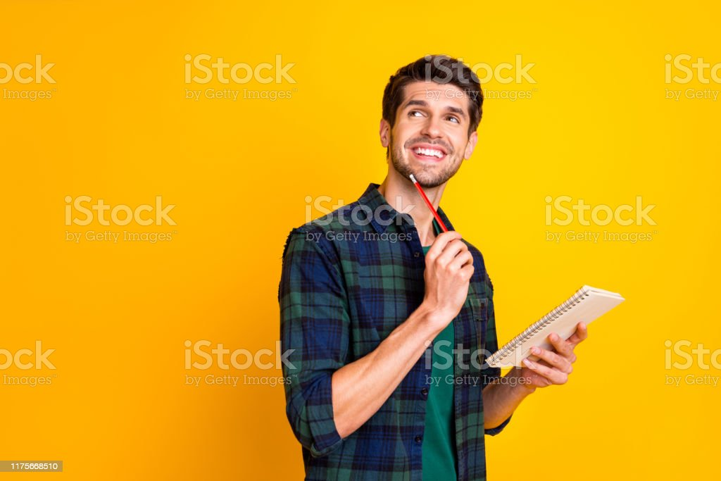 Photo of nice guy with organizer in hands making notes creating startup idea wear casual checkered shirt isolated yellow color background Photo of nice guy with organizer in hands making notes creating startup, idea wear casual checkered shirt isolated yellow color background Adult Stock Photo