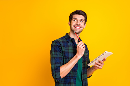 Photo Of Nice Guy With Organizer In Hands Making Notes Creating Startup Idea Wear Casual Checkered Shirt Isolated Yellow Color Background Stock Photo - Download Image Now