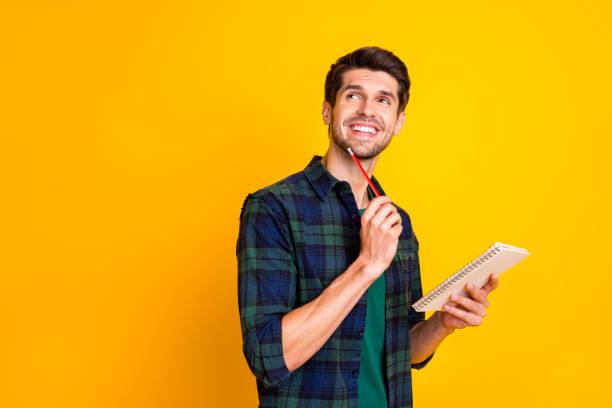Foto von netten Kerl mit Veranstalter in den Händen machen Notizen erstellen Start-up-Idee tragen lässig kariert Shirt isoliert gelb Farbe Hintergrund – Foto