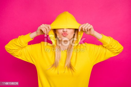 Photo of nice lady hiding, eyes with hood sending air kiss wear yellow hoodie pullover isolated pink background