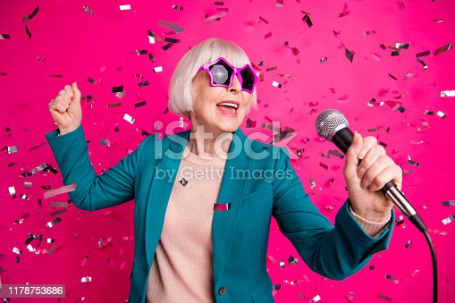 Photo of old mature stylish energetic woman singing in microphone, wearing star shaped spectacles standing in falling confetti isolated over pink vivid color background