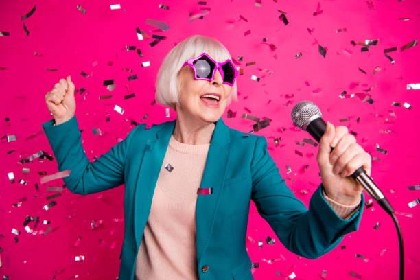 foto av gamla mogna snygga energisk kvinna sjunger i mikrofonen bär stjärnformade glasögon stående i fallande konfetti isolerade över rosa levande färg bakgrund - celebrities of age bildbanksfoton och bilder