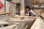 istock Photo of one African-American female carpenter using circular 1254563055