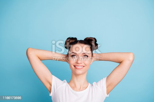 1054970060istockphoto Photo of overjoyed lady holding behind head look up empty space wear white casual t-shirt isolated blue background 1166173595