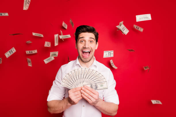 photo of overjoyed nice good attractive handsome man having won lottery while isolated with red background - throw money away stock pictures, royalty-free photos & images