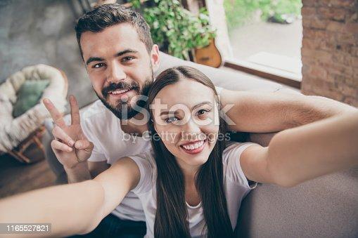 Photo of perfect, just married pair in love spending honeymoon making selfies sitting sofa indoors