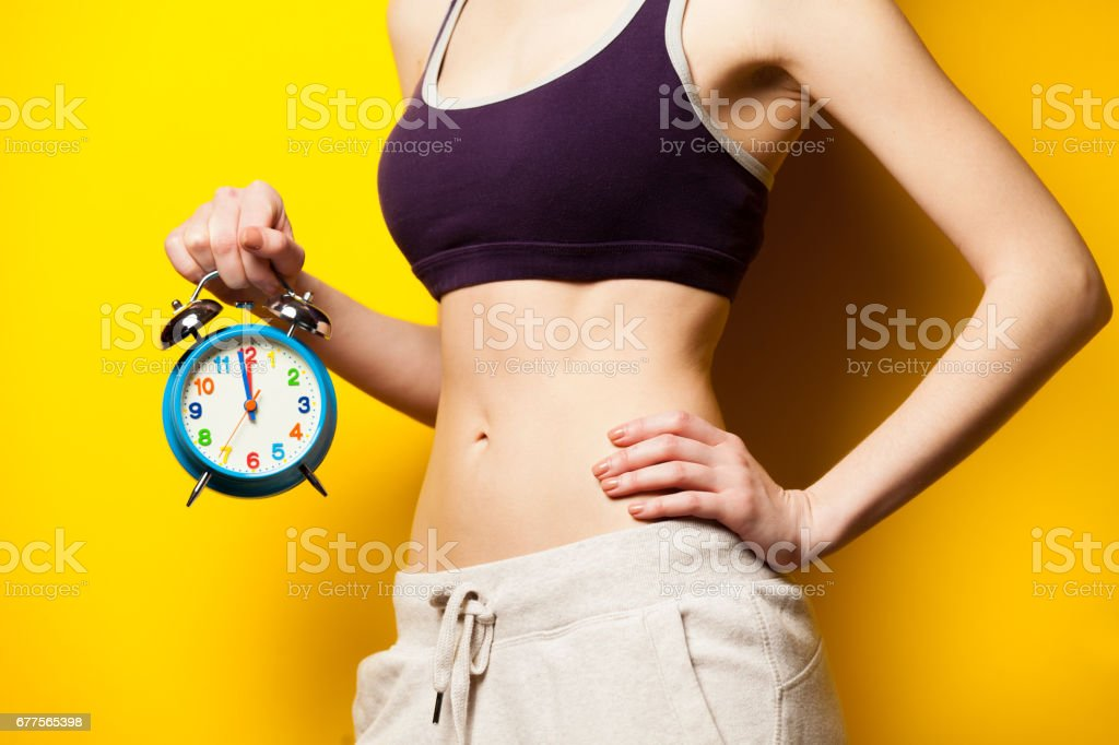 photo of perfect slim female body with alarm clock in the hand on the wonderful yellow background royalty-free stock photo
