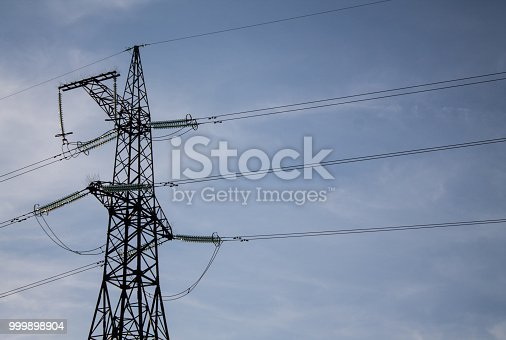 istock Photo of power transmission tower. High voltage pillar on blue sky background 999898904