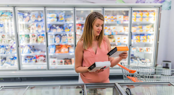 Photo of pregnant Woman buying vegetables in frozen section in supermarket stock photo