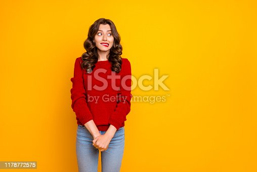 Photo of pretty curly wavy charming cute cheerful nice good girlfriend, standing hesitating and shy looking away at something with hands folded isolated over yellow vivid color background