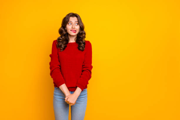 Photo of pretty curly wavy charming cute cheerful nice good girlfriend standing hesitating and shy looking away at something with hands folded isolated over yellow vivid color background Photo of pretty curly wavy charming cute cheerful nice good girlfriend, standing hesitating and shy looking away at something with hands folded isolated over yellow vivid color background shrugging stock pictures, royalty-free photos & images