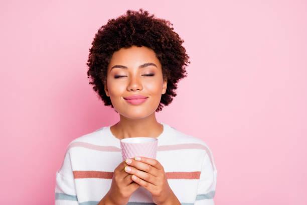 사진 의 예쁜 어두운 피부 아가씨 들고 손 뜨거운 음료 컵 꿈꾸는 닫는 눈 을 즐길 좋은 냄새 착용 스트라이프 풀오버 고립 된 파스텔 핑크 색상 배경 - 향기로운 뉴스 사진 이미지