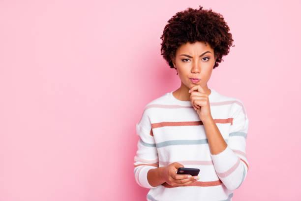 foto van vrij donkere huid dame houden telefoon beslissen wat opmerking te schrijven hand touch chin wear wit gestreepte pullover geïsoleerd pastel roze kleur achtergrond - achterdocht stockfoto's en -beelden